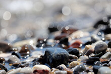 Wet Pebble Stones On Blurred Background Of Sea Waves. Summer Vacation Concept