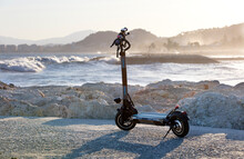 Electric Scooter With Sea With Waves In The Background At Sunset