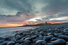 The Most Beautiful Sunrise At Dunstanburgh Castle With The Famous Slippery Black Boulders In Northumberland, As The Sky Erupted With Colour