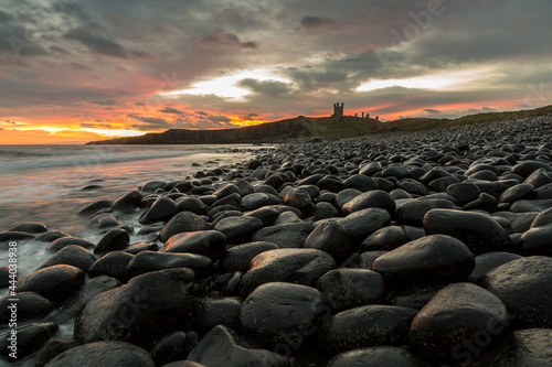 The most beautiful sunrise at Dunstanburgh Castle with the famous slippery black Fototapet