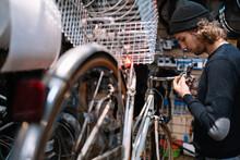 Man Working In Repairing Bicycle Workshop