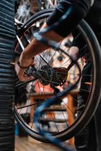 Crop Man Repairing Gear Cassette Of Bicycle In Garage