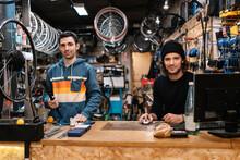 Cheerful Mechanics Working In Bicycle Repair Service Workshop