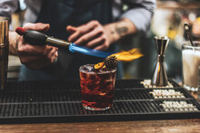 Bartender Making A Smoky Cocktail With A Torch