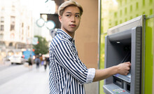 Asian Man Using ATM In Street