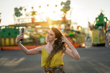Happy Woman Taking Selfie On Smartphone At Fairground