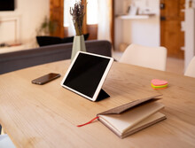 Tablet And Notebook Placed On Wooden Table