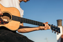 Young Man Sitting Playing Acoustic Guitar On A Rooftop