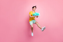 Photo Of Pretty Funny Young Guy Dressed Yellow Shooting Water Gun T-shirt Jumping High Isolated Pink Color Background