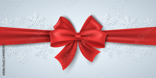 Christmas red ribbon with bowknot on the background of paper snowflakes Poster Mural XXL