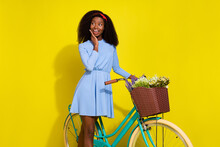 Photo Of Amazed Curious Brunette Afro American Lady Wear Blue Dotted Dress Look Empty Space Ride Bike Isolated On Yellow Color Background