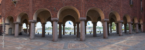 Fotografie, Obraz Colonnade at the Stockholm Town City Hall at sunset a summer day.