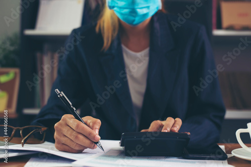 Fotografia, Obraz Budget planning concept, Accountant wear mask is calculating company's annual tax