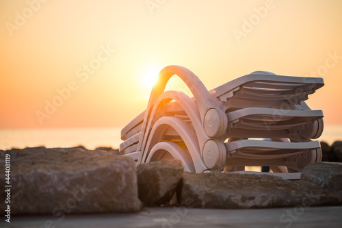 Obraz na plátne White Plastic Sun Loungers At The Beach On Vacations At Sunset