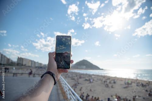 Murais de parede una mano con un móvil sacando una foto a la playa de la zurriola en San Sebastian