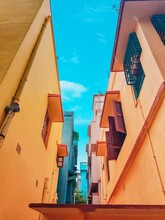 Two Orange Colour Buildings From Which The Blue Sky Is With Some White Cloud Is Clearly Visible