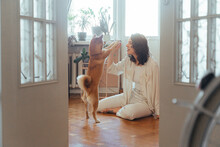 Young Woman Spends Time At Home With Her Dog
