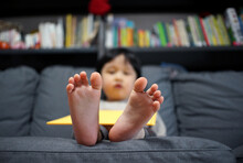 Close-up Of Cute Asian Chinese Baby Boy's Feet Sitting On Sofa At Home