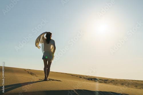 Fotografie, Obraz Woman standing on wavy sand dunes in desert landscape at golden sunset light and wind