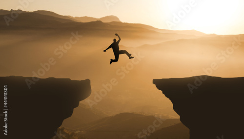Tablou Canvas Silhouette jumping cliff sunset mountain