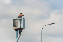 A Half-naked Technician On A Lifted Aerial Work Platform Installing New Street Lighting.