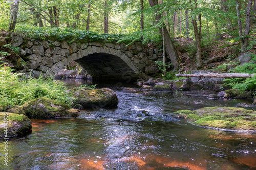 old stone arched bridge in woods with brook stream Fotobehang