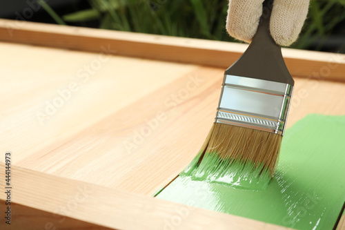 Worker applying green paint onto wooden surface, closeup. Space for text