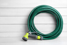 Green Garden Hose With Spray Gun On White Wooden Table, Space For Text