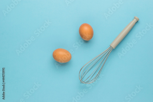 Fotografia, Obraz Two brown eggs and a whisk for whipping on a blue background.