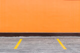 Fototapeta Kawa jest smaczna - Orange Building Wall And Parking Spaces With Painted Yellow Dividers