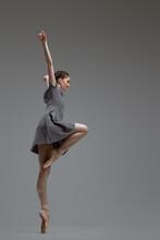 Flexible Ballerina Wearing Gray Dress Against Gray Background
