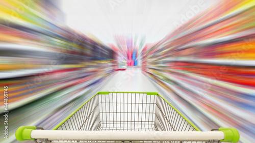 Fotografía Supermarket aisle with empty green shopping cart