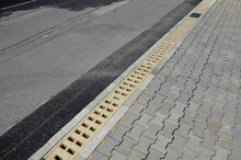 Across The Path There Is A Channel With A Metal Grid For Drainage Interlocking Paving. The Water Is Drained From The Surface Into The Gutter And Further Into The Rain Sewer