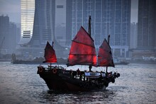 Traditional Boat On Sea By Buildings In City