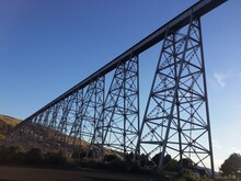 Low Angle View Of Train Tressel Against Blue Sky