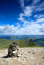 Looking Down Striding Edge Towards Ullswater And Glenridding From The Summit Of Helvellyn In The Lake District. Shot In Portrait With A Stone Cairn In The Foreground