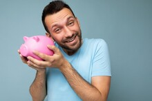 Closeup Of Happy Positive Smiling Young Handsome Brunet Unshaven Man With Beard With Sincere Emotions Wearing Casual Blue T-shirt Isolated Over Blue Background With Copy Space And Holding Pink Pig