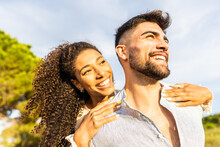 Multiracial Happy Young Beautiful Couple In Love Having Fun Outdoor In Nature At Dusk Looking At Horizon Kissed By The Setting Sun. Toothy Smiling Afro-American Girl Embracing From Back Her Boyfriend