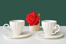 Two Coffee Cups And A Red Rose On A Green Background