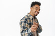 You got this. Smiling confident african american man, looking satisfied, praise and compliment person, pointing finger at camera, inviting or congratulating someone, standing over white background