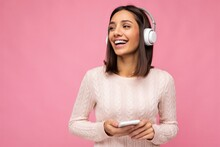 Photo Of Beautiful Joyful Smiling Young Woman Wearing Stylish Casual Clothes Isolated Over Background Wall Holding And Using Mobile Phone Wearing White Bluetooth Headphones Listening To Music And