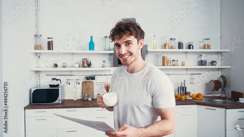 Photo happy man with cup of coffee and morning newspaper smiling at camera in kitchen