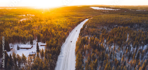 Canvastavla Aerial view from drone of nature landscape capped with snow and surrounded by coniferous forest, bird's eye view of of snowy trees in national park of north Lapland in winter, road with cars