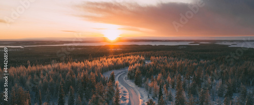 Fotografiet Aerial view from drone of snowy peaks of endless coniferous forest trees in Lapl