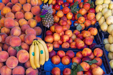Counter At The Farmers' Market With Ripe Peaches, Bananas, Pineapple, Pears. Fruit Trade.