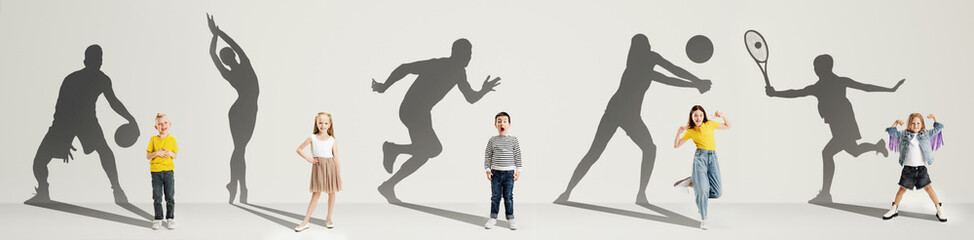 Collage. Dreams about big and famous future. Conceptual image with little boys and girls and shadows of fit professional sportsmen on light gray background
