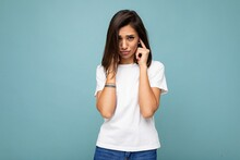 Portrait Of Upset Offended Young Attractive Brunet Woman With Sincere Emotions Wearing White T-shirt For Mockup Isolated On Blue Background With Empty Space And Covering Ears