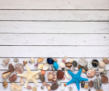 Layout For Travel: Starfish, Colorful Pebbles And Shells For Traveling. With A Wooden Background. A Place To Copy.
