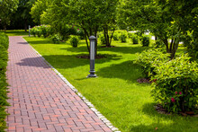 Straight Stone Tile Pavement In A Park Landscaped With Green Grass And Bushes With Tree Bark Mulching, Garden Landscape With Ground Iron Street Lights On A Sunny Summer Day.
