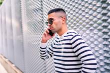 Trendy Guy Speaking On Smartphone Near Wall